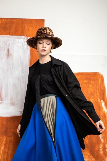 Синяя юбка асимметричного кроя с вставкой из плиссированного белого хлопка.