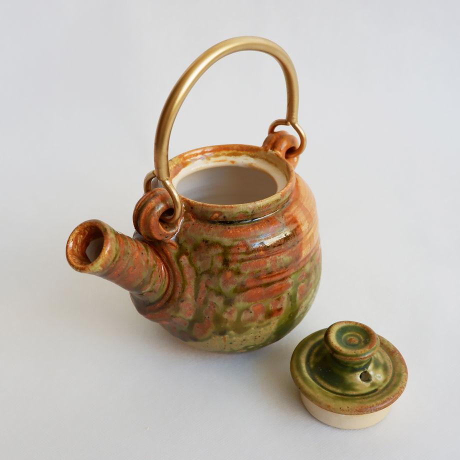 Яркий керамический заварной чайник.